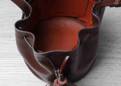 Sac sô : sac type mangeoire, bandoulière réglable, extérieur veau brun cognac et doublure agneau couleur brique. Fermeture par 2 pompons asymétriques et lien avec coulant. Cousu main principalement